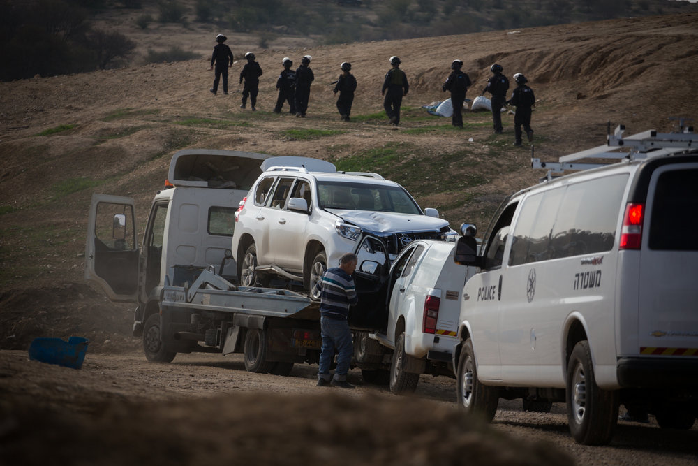 A tow truck removes the car driven in an alleged car ramming attack, killing an Israeli police man, during clashes and protests against demolition of homes in the Bedouin village of Umm al-Hiran in the Negev desert, Southern Israel, January 18, 2017. The Bedouin driver was shot dead under suspicion of being a terrorist. Photo by Hadas Parush/Flash90