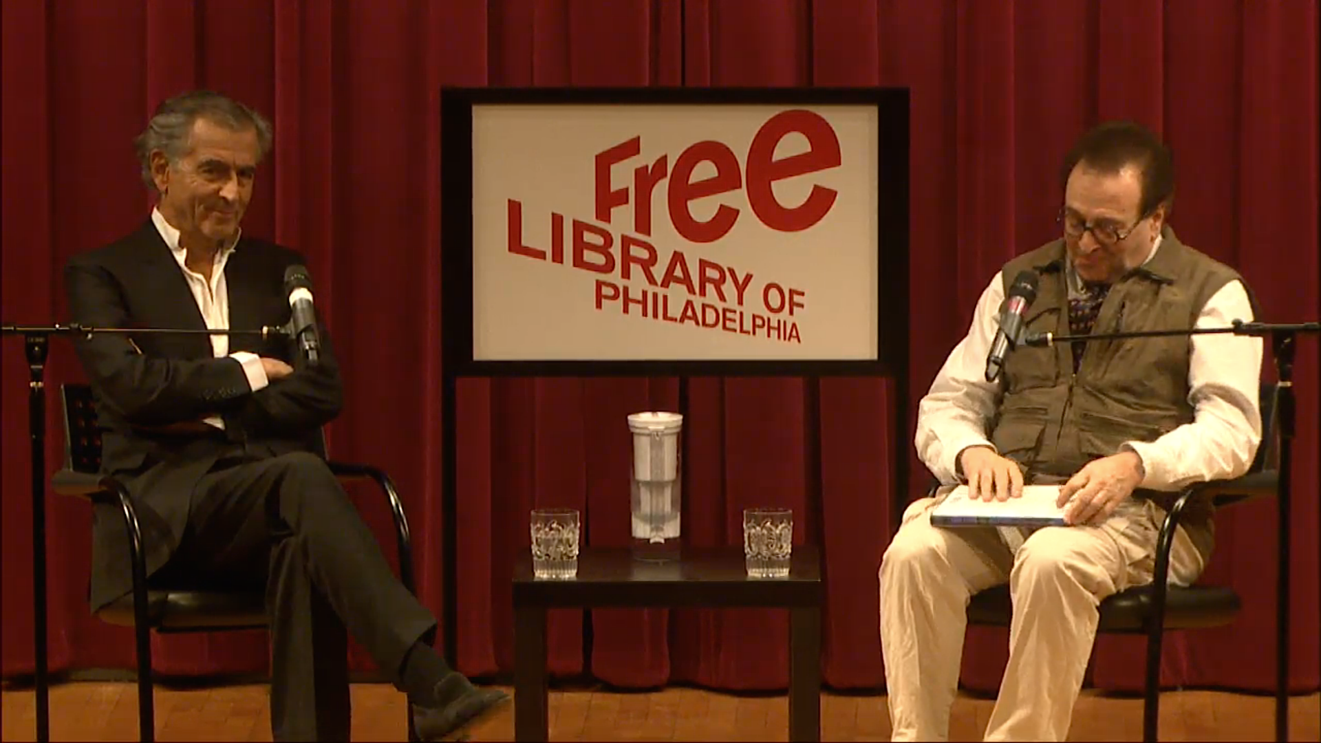 Bernard-Henri Lévy, left, waits for a question from Carlin Romano, right, in a screenshot from the Livestream of Lévy's appearance at the Free Library.