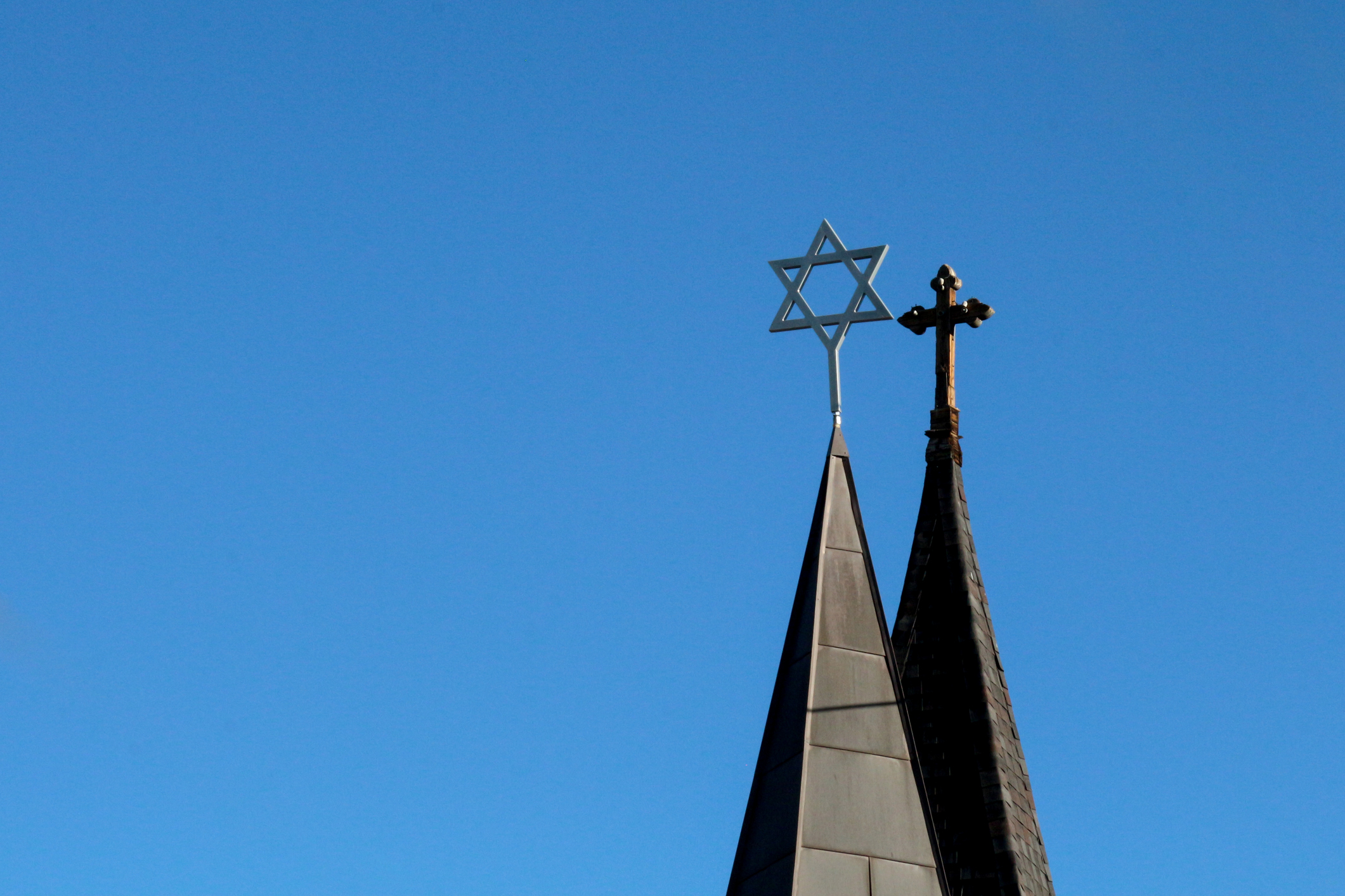 side by side spires with cross and star of david jewish exponent