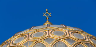 a synagogue roof with a gold star on david on top