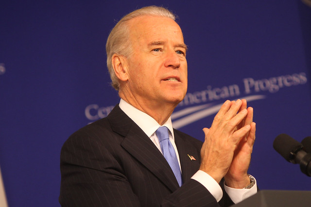 Joe Biden looking up and clasping hands together onstage
