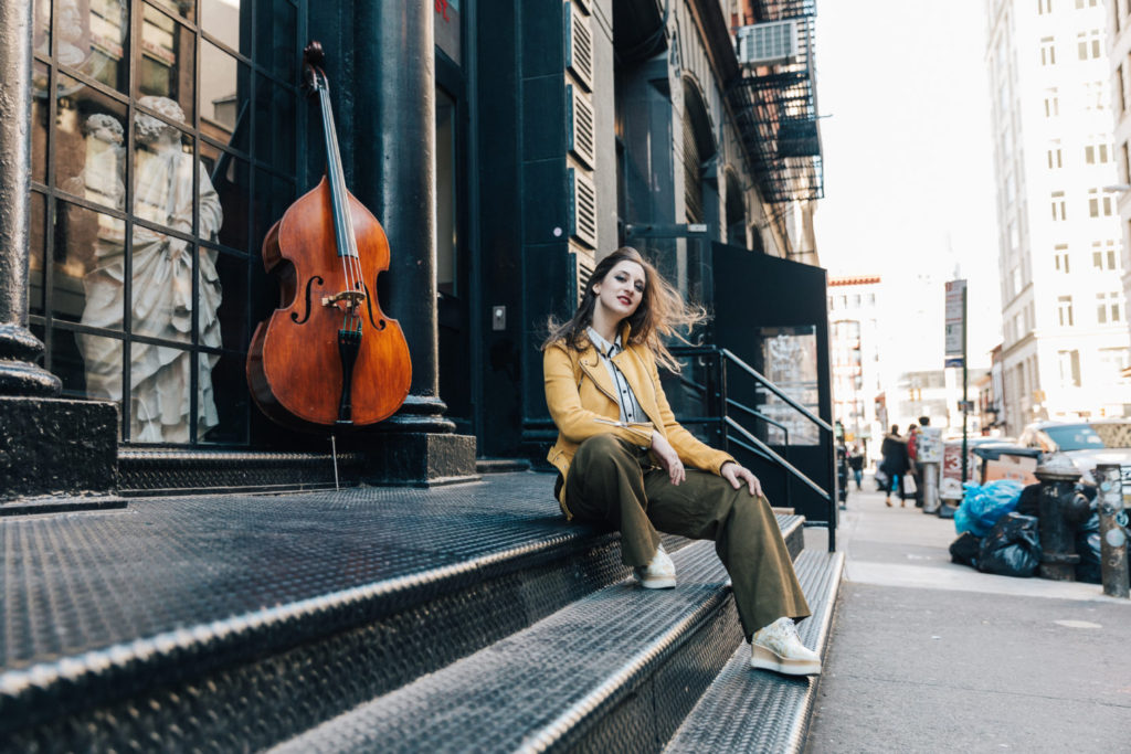 Adi Meyerson sitting on steps next to a bass