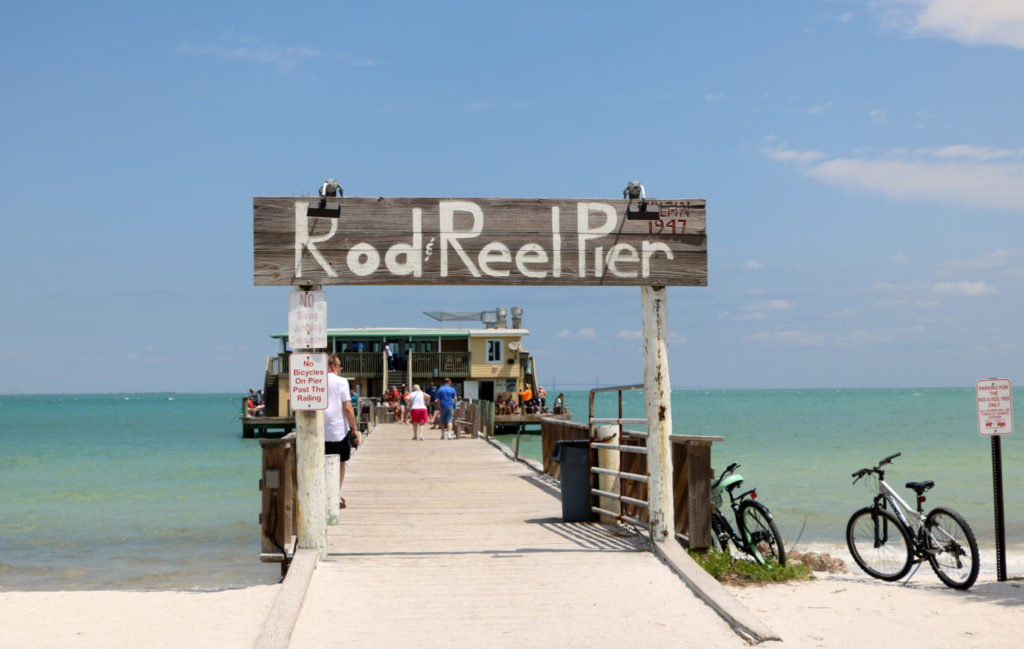 "A pier with a sign that says ""Rod Reel Pier"" next to a bicycle"