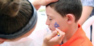 A woman paints a Jewish star on a boy's cheek