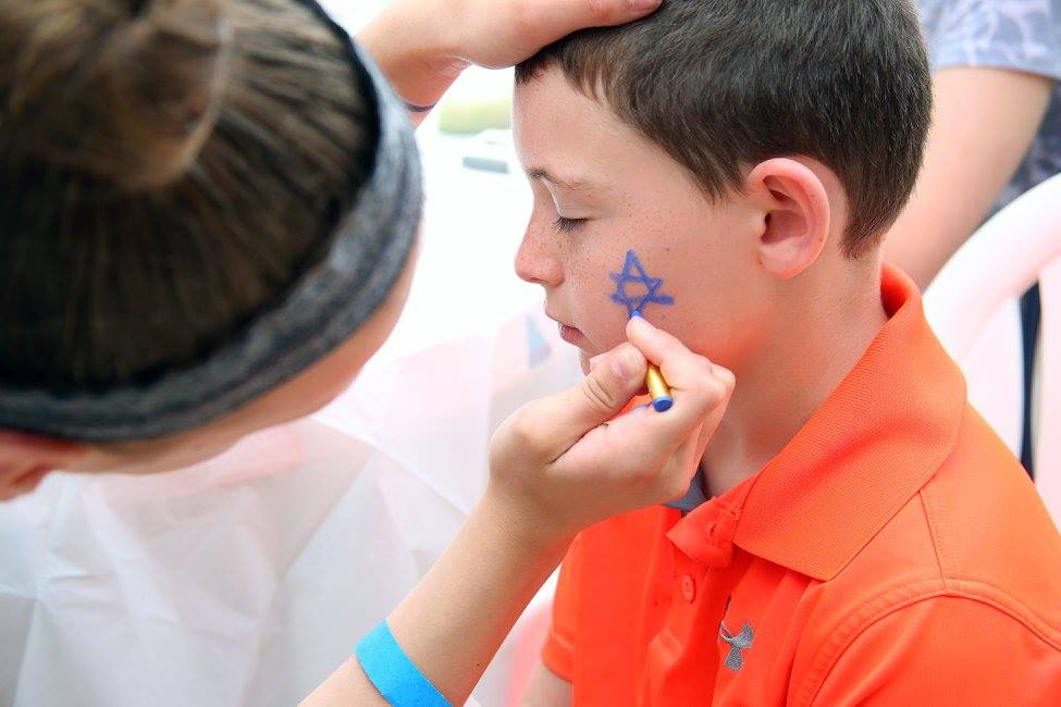 A woman paints a Jewish star on a boy's cheek