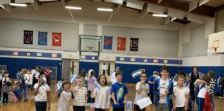 PJDS students holding Israeli flags in a gym