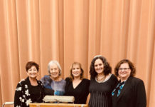 Barbara Nussbaum, Diane Steinbrink, Rabbi Lynda Targan, Rabbi Shoshana Tornberg and Rabbi Andrea Merow stand at a opinion with the NCJW logo