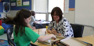 Beverly Bernstein plays a board game with students