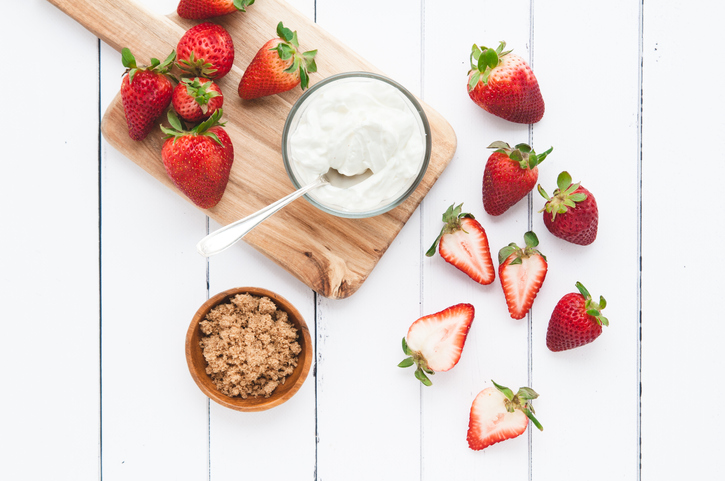 a bowl of sour cream and a bowl of brown sugar alongside halved strawberries