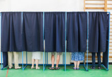 A row of people behind curtains in voting booths