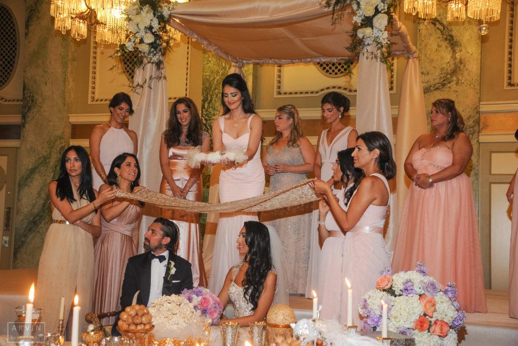 Michael Tuteur and Maryam Nezamzadeh sit at the sofreh at their Jewish-Muslim wedding