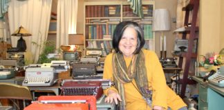 Pam Rogow sits in her shop surrounded by typewriters