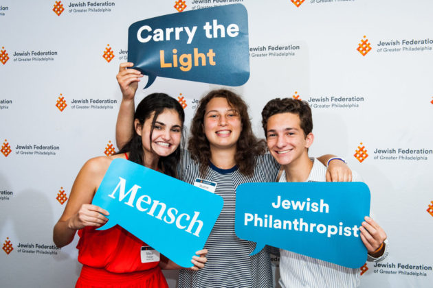 Participants Maya Posner, Ruthie Meles and Isaac Kesier hold signs that say mensch, carry the light and jewish philanthropist