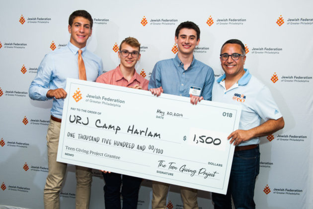 Second-year participants Justin Badt, Max Kahn and Seth Richards present their award to Aaron Selkow of UJR Camp Harlam.