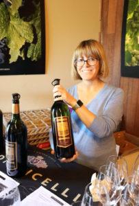 Montse Reece holds a bottle of wine