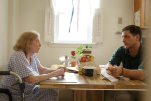 A Northeast NORC employee speaks with a Holocaust survivor at a table