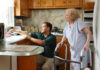 An employee of the Jewish Federation's Northeast NORC assists a Holocaust survivor in her kitchen