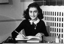 A black and white photo of anne frank at a desk