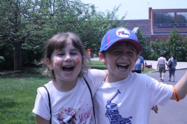 Two children, one with face paint, laugh