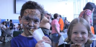Two kids, one with face paint, eat big pretzels
