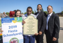 Elaine Lindy holding a sign that says 2019 fiesta schoolyards, Yasir Roundtree holding a sign, Otis Hackney and Alan Lindy