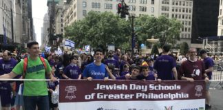 Rabbi Chaim Galfand, Judah Troodler, Itai Schwartz, Adir Schwartz and Zev Jacobson hold a banner
