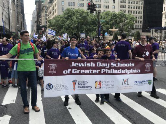 Rabbi Chaim Galfand, Judah Troodler, Itai Schwartz, Adir Schwartz and Zev Jacobson hold a banner