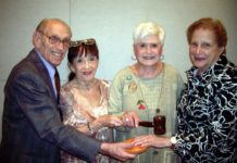 From left: Alvin and Evelyn Jacobs, retiring co-presidents of the Maris Grove Jewish Community, pass the gavel and block to incoming co-presidents Berrie Grossman and Eddi Chaikin