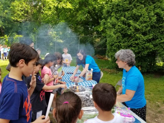 Sarah Chairnoff and Leslie Kornsgold (in blue T-shirts) make s'mores with the students.