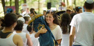 A camper at a Jewish summer camp holds a Torah scroll surrounded by other campers