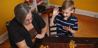 A woman and a young boy play dreidel