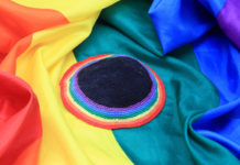 Rainbow colored kippah over rainbow flag
