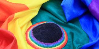 Rainbow colored kippah over rainbow flag