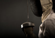 A side view of a fencer holding a sword