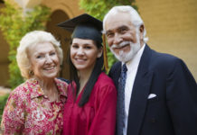 A graduate at commencement with grandparents