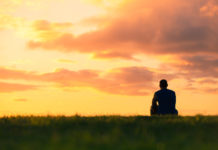 A lone man sits before a sunset, trying to ease the negativity in his thinking