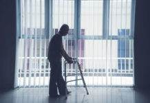 Silhouette of elderly man walking with a walker near a window