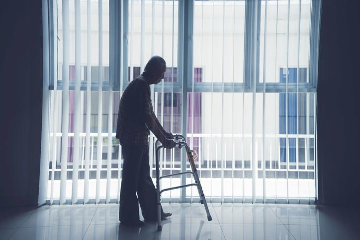 Silhouette of elderly man walking with a walker near a window