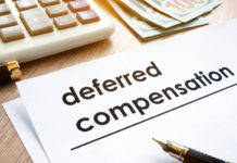 A paper on a desk reads deferred compensation