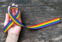 A rainbow LGBTQ ribbon rests in someone's hand