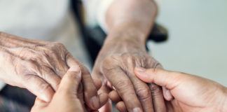 A person holds an elderly person's hands