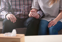 a couple holds hands on a couch next to a box of tissues