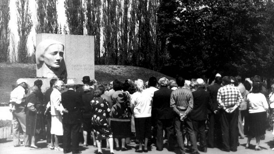 "A group of people surrounds ""The Grieving Mother"" monument to Holocaust victims in Poltava, Ukraine"