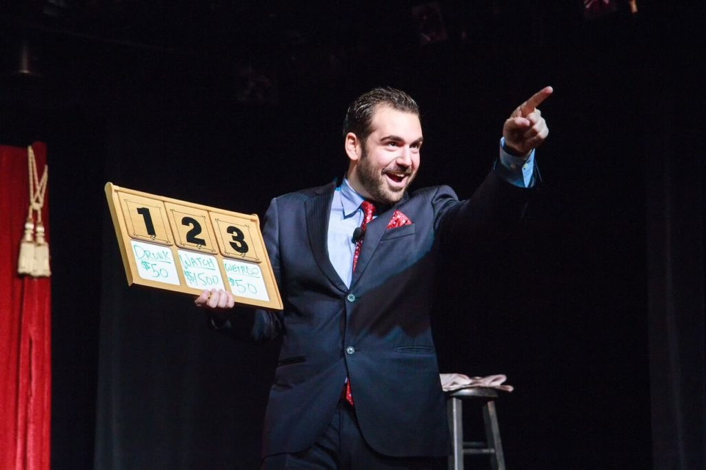 Harrison Greenbaum performs a bit about The Price is Right, while holding a board that says 1, 2, 3 and pointing