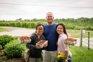 A man and two women stand in a field holding crates of strawberries