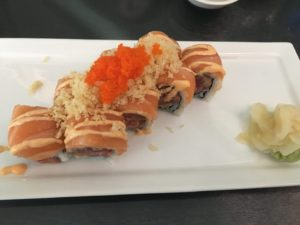 A sushi roll topped with fish and roe