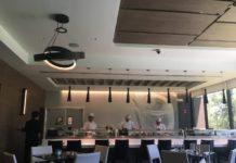 Several chefs work behind a bar making sushi at B2