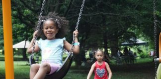 A girl swings on a swing while another girl pushes her