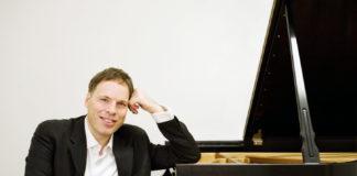 Alon Goldstein sitting next to a piano