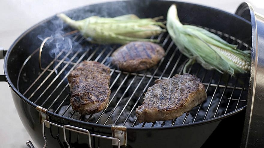 kosher beef and corn on the cob on a charcoal barbecue grill